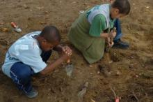 Two children dig in the dirt